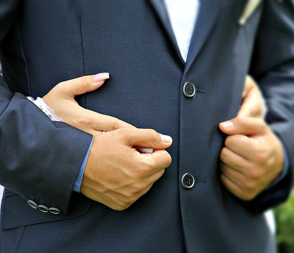 How to Remove Perfume Smell from Clothes Without Washing Them: Man in suit being hugged.